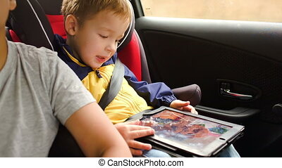 Happy boy playing game on pad during car travel