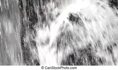 Water flowing over dark rocks - Video of fast moving water...