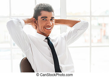 Make a small pause in your work! Handsome young Afro-American man in shirt and tie holding hands behind head and smiling while sitting at his working place