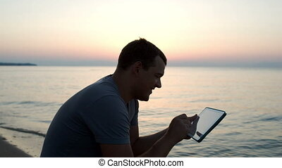 Man using tablet computer on the beach