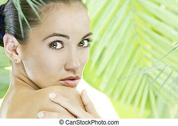 spa - portrait of young beautiful woman on green leafs back