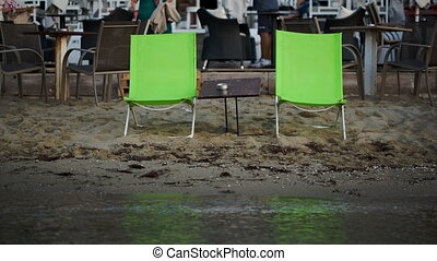 Two empty chaise-lounges with table on the beach - Two empty...
