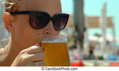 Young woman drinking cold beer on a hot day - Close-up shot...