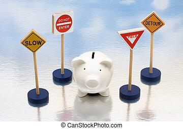 Risky Investments - Piggy bank sitting next to a road signs,...