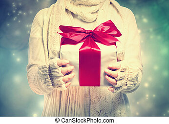 Gift box with red ribbon in the snowing night - Woman...