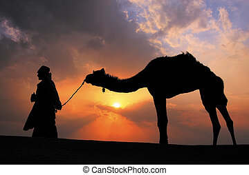 Silhouetted bedouin walking with his camel at sunset, Thar...