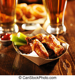 barbecue buffalo chicken wings served with beer, celery, and ranch