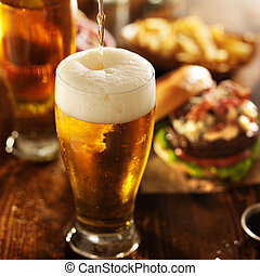 ice cold beer pouring into glass with burgers at restaurant...