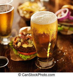 cold beer with foamy head and burgers