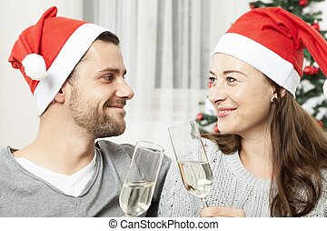 young christmas couple with champagne smiling in front od...