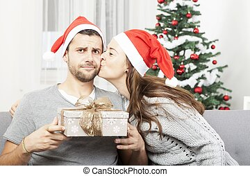 man is sceptical about christmas gift while his girlfriend...