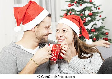 young christmas couple happy on sofa - young christmas...
