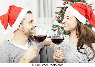 young couple enjoy chistmas with wine - happy young couple...