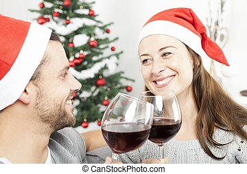 couple enjoy chistmas with wine on sofa - happy young couple...
