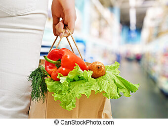 at the grocery store - a woman holding a bag of fruit