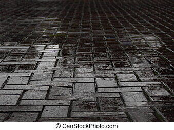 Wet black brick road after heavy rainfall