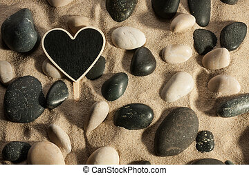 Close-up of stones and heart sticking out of the sand in the sun