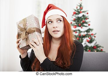 girl is shaking happy christmas present - young red haired...