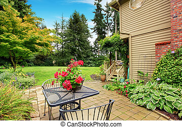 Walkout patio with table set and flower pot - Backyard with...