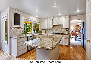 Kitchen room with white storage combination and island -...