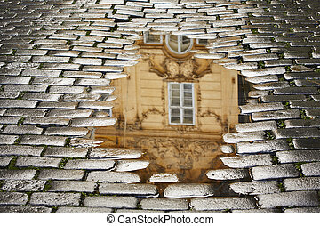 After rain in Prague - reflection of the house in puddle