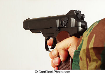 Hand in camouflage uniform with semi-automatic pistol - Hand...