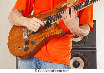 Hands of man put guitar chords closeup