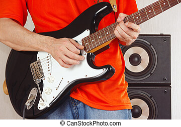 Hands of musician playing the electric guitar closeup