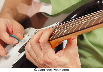 Hands of rock guitarist put guitar chords closeup - Hands of...