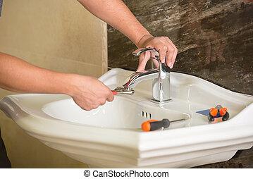 Plumbing - Plumber is repairing an hot-water heater in...