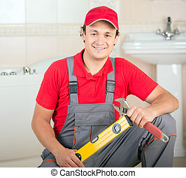 Plumbing - Plumber with the building level and wrench during...