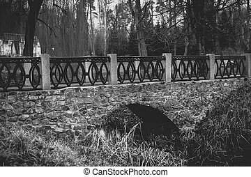 Monochrome view of old stone bridge over river at park
