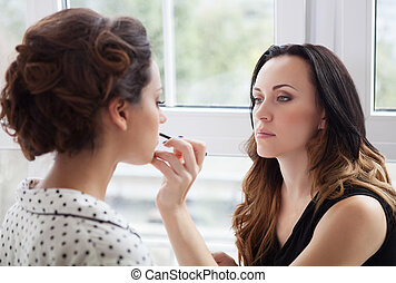 Make-up artist doing make up for young beautiful bride...