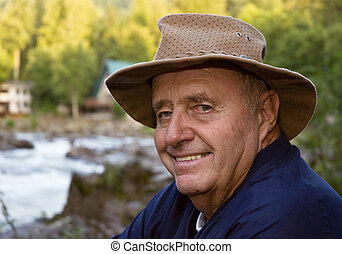 Active Senior male fisherman with river in background -...
