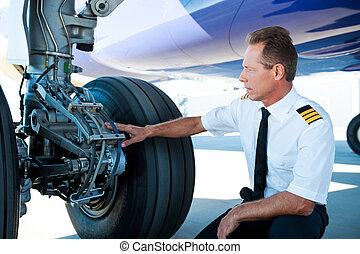 Checking the wheels. Confident male pilot in uniform...