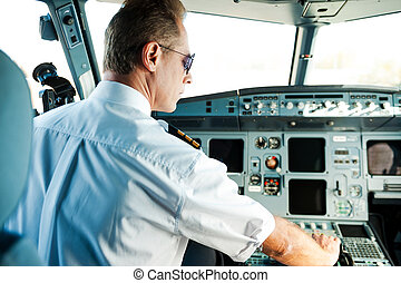 Ready to take off. Rear view of confident male pilot sitting...