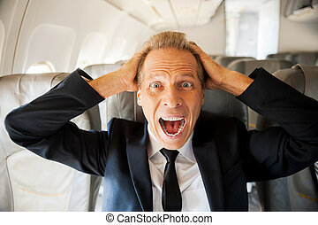 Fear of flight. Shocked mature businessman touching his head...