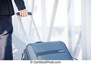 Business trip. Close-up of businessman carrying suitcase...