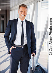 Executive on the Go. Confident mature businessman carrying...