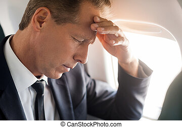 Feeling headache. Frustrated mature businessman touching his...