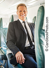 Ready to flight Confident mature businessman sitting at his...