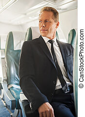 Businessman in airplane Confident mature businessman sitting...