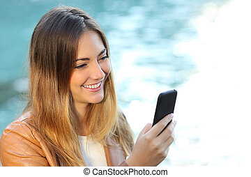 Casual woman using a smart phone with the sea in the...