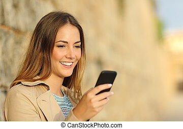 Happy woman using a smart phone in an old town - Portrait of...