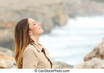 Woman breathing fresh air in winter on the beach with the...