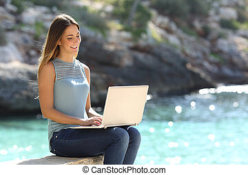 Woman typing on a laptop in a tropical beach with a...