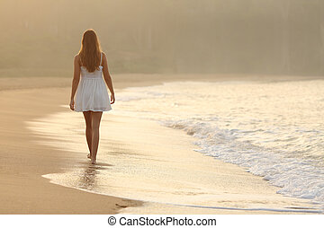 Woman walking on the sand of the beach