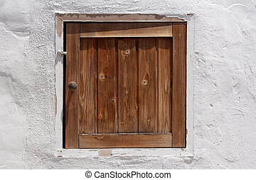 vintage wooden shutter in whitewashed wall