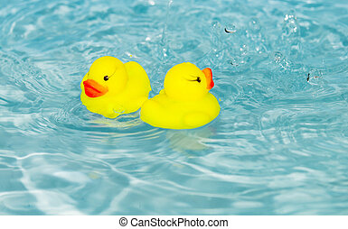 two rubber ducklings floating on a water