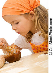 Little girl making cookies series - dosing the filling